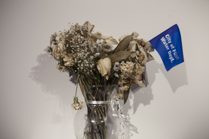 "Justin Poppe's vase of flowers with a pennant that reads ""City of Flint Water Dept."""